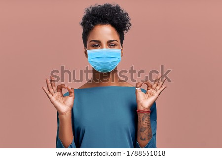 Kind Hearted African American Female Paramedic Wearing Respiratory Mask from Coronavirus Disease During COVID-19 Epidemic, Says Good Job or Well Done, Makes Okay Gesture, Symbol of Approval and Like