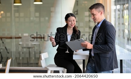 Kind male leader executive manager share and discuss business solutions plan ideas on tablet with young female marketing manager in office.