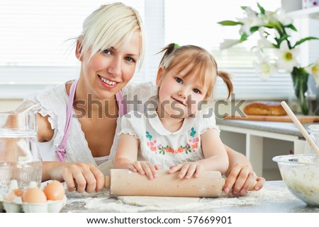 Kind mother and child baking cookies in the kitchen