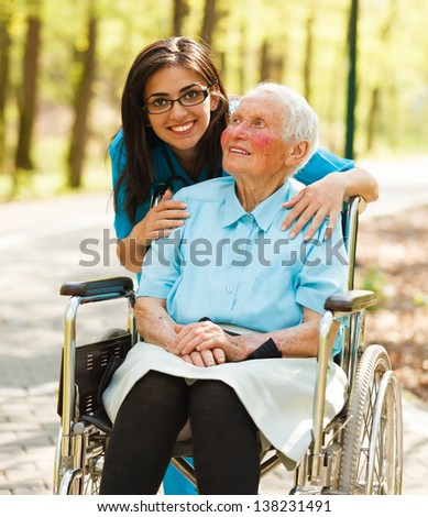 Kind nurse taking care of elderly lady patient in wheelchair.