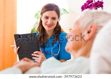 Kind nurse with clipboard in her hands registering senior woman\'s healthcare stats.