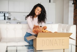 Kind smiling African American female volunteer with curly hair sitting on a sofa, packing toys in a cardboard box for reuse, donating to charity, for orphans, in anticipation of the joy of children
