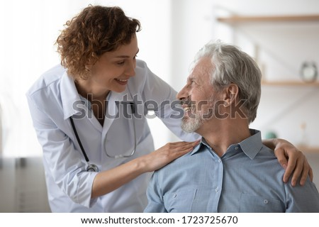 Kind smiling female doctor embracing encouraging happy senior male patient in hospital. Happy healthy older man and his physician enjoying talking at nursing home. Elderly medical health care concept.