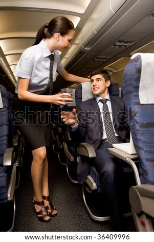 Kind stewardess giving glass of water to young businessman in airplane