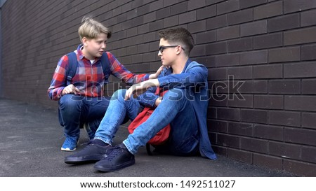 Kind teenage boy starting friendship with bullied student, helpline for children