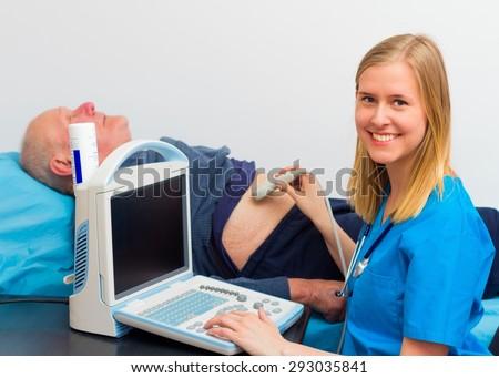 Kind young doctor examining elderly patient\'s hernia on the echograph.