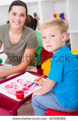 kindergarten boy and female teacher in classroom - stock photo