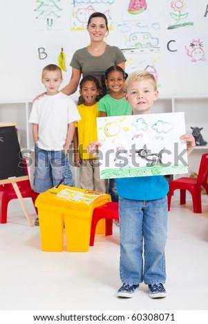kindergarten boy holding his paint in front of classmates
