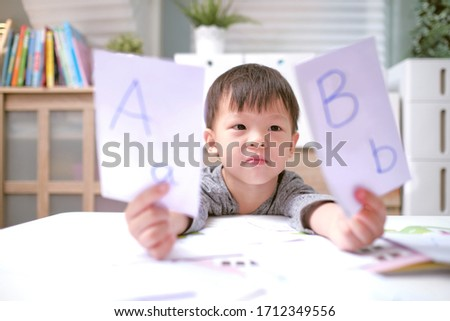 Kindergarten boy playing with flash cards , Asian children learning English with flash cards, Teach young kids English at home, Child at home, kindergarten closed during the Covid-19 health crisis stock photo