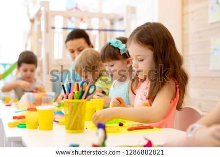 kindergarten children doing arts and crafts with teacher in day care centre