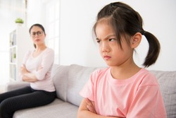 kindergarten children is scolded by school teacher and feel angry sitting in the sofa area of the classroom and the blurred teacher looked at her seriously in the background.