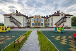 Kindergarten preschool building with big windows. Architecture and development concept.
