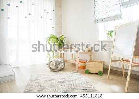 Kindergarten room with easel chair and table for painting. children\'s room and furniture and natural green flowers on white windowsill