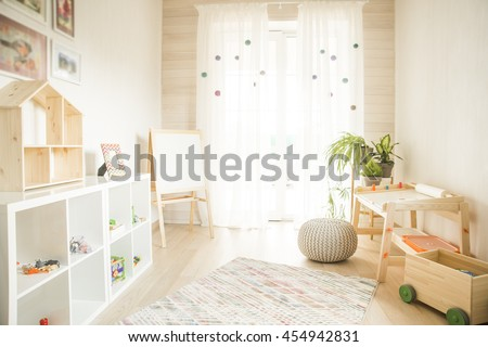 Kindergarten room with easel chair and table for painting. children's room and furniture and natural green flowers on white windowsill
