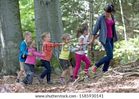 Kindergarten teacher playing with kids in a wood kindergarten