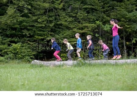 Kindergarten teacher playing with kids on log in a wood kindergarten