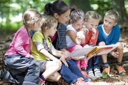 Kindergarten teacher reading with kids in a wood kindergarten