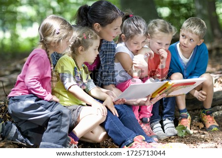 Kindergarten teacher reading with kids in a wood kindergarten
