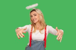 Kindness and generosity. Portrait of angelic beautiful adult woman with nimbus above head holding outstretched hands and smiling, giving free hugs. indoor studio shot isolated on green background