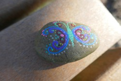 Kindness rock with artsy butterfly painted on