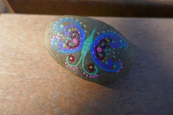 Kindness rock with painted artsy butterfly