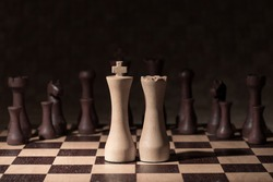 King and Queen in a wooden chess game against the odds with the opposition