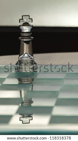 King chess piece - business concept series with chess -  strategy, CEO, director, leadership. Reflection of king on chess board. Business card, with copy / text space.