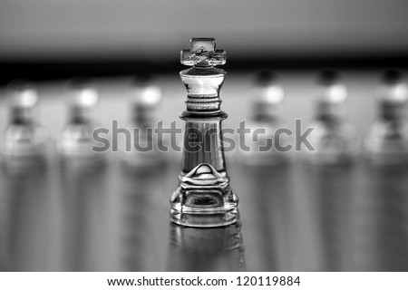 King chess piece (pawns blurred in background) as a business concept series -  leadership, mentor, CEO, coaching, business guru, consultant. With text  or copy space for business card design.