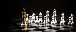 King chess standing to fight battle combat with silver chess on chess board. Concepts of business team and leadership strategy and organization risk management.
