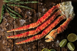 King crab leg with rosmary, lime and melting ice cubes on dark wooden background
