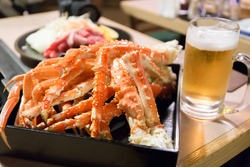 king crab legs and a glass of beer