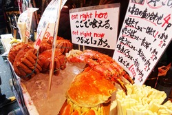 King Crab meat selling at Fish Market, Japan. (Translation: 1. Please Try 2. Special 4 mixed of the Day/Scallop 1pc+Oysters2pc/Carb+Oyster Set/Japanese Tuna+Oyster Set, All set at 1000 Yen)
