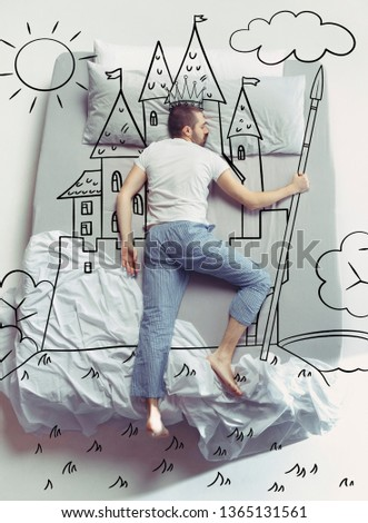 King of the family. Top view photo of young man sleeping in a big white bed at home. Dreams concept. Painted dream about kingdom, castle, crown, sun, landscape, power, control, fairy world, pikestaff. #1365131561