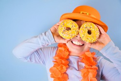 King's Day in Holland. Traditional festival on April 27 in the Netherlands. A little girl in a festive orange hat holds in hands colored donuts. Copy space