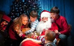 King Santa Clause giving Christmas Presents to Happy Children in the Christmas Night