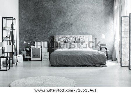 King-size bed against dark textured wall in monochromatic bedroom with screen and white carpet #728513461