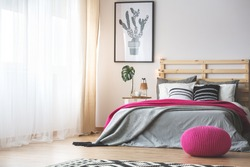 King-size bed in bright bedroom with pink accessories