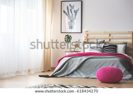 King-size bed in bright bedroom with pink accessories #618434270