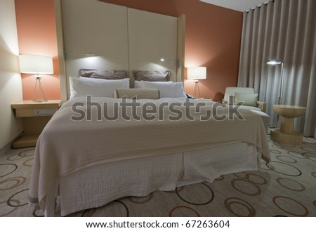 King-size bed with bedside table armchair  lamps and curtain