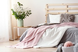 King-size bed with grey sheets and pink blanket standing in bright bedroom interior with fresh plants in vase and window with drapes