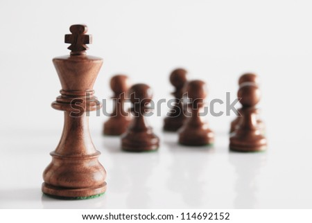King with chess pawns in the background