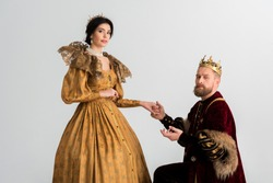 king with crown bending on knee and holding hands with queen isolated on grey