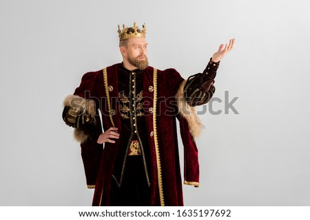 king with crown pointing with hand isolated on grey Stockfoto ©