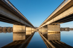Kings Avenue Bridge, Canberra, ACT across Lake Burley Griffin, with symmetrical reflections in water. Blue sky and warm afternoon, pre-sunset light hitting concrete bridge. View from south side.