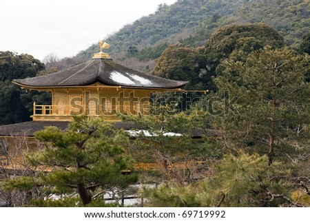 Kinkaku-ji (The Golden Pavilion), Rokuon-ji Temple, Kyoto, Japan. View of harmonious setting of pavilion in winter showing forest colors and upper floors finished in gold-leaf on Japanese lacquer.