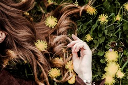 Kinky female brown hair on green grass and yellow colors of a kulbub. Natural hair care