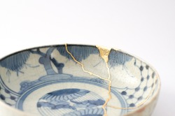 Kintsugi antique japanese plate. Gold cracks restoration on old Japanese pottery restored with the antique restoration technique.The unique beauty of imperfections.