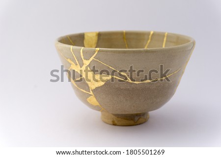 Kintsugi beige tea ceremony chawan. Gold cracks restoration on old Japanese pottery restored with the antique Kintsugi restoration technique. The beauty of imperfections.