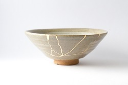 Kintsugi bowl. Gold cracks restoration on old Japanese pottery restored with the antique restoration technique.The unique beauty of imperfections.
