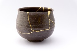 Kintsugi brown tea ceremony chawan. Gold cracks restoration on old Japanese pottery restored with the antique Kintsugi restoration technique. The beauty of imperfections.
